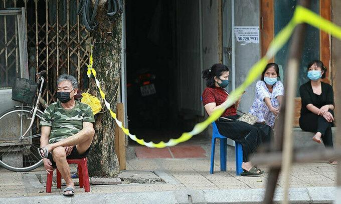 Les gens s'assoient devant leurs maisons sur la rue Truc Bach qui a été mise sous séquestre le 6 mars 2020. Photo de VnExpress / Giang Huy.