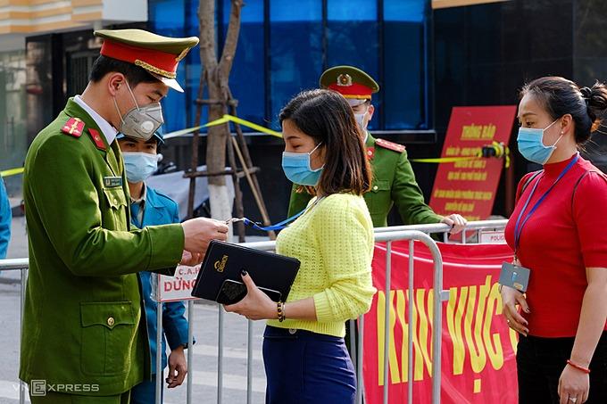 Les agents de police locaux vérifient les personnes qui entrent dans la rue Truc Bach. Photo de VnExpress / Giang Huy.
